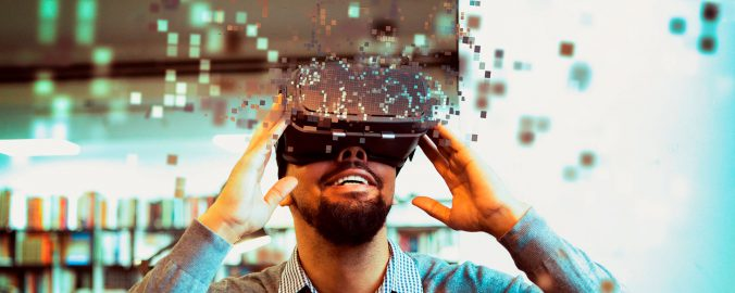 A man looking through a virtual reality headset.