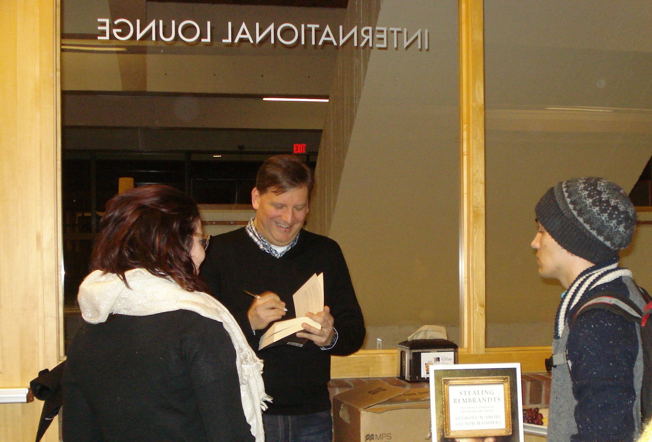"Anthony Amore signs copies of his book ""Stealing Rembrandts,"" after his lecture."