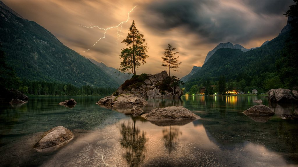 Photo of a lake, small island, trees, mountain, sky, and buildings representing bio-diversity