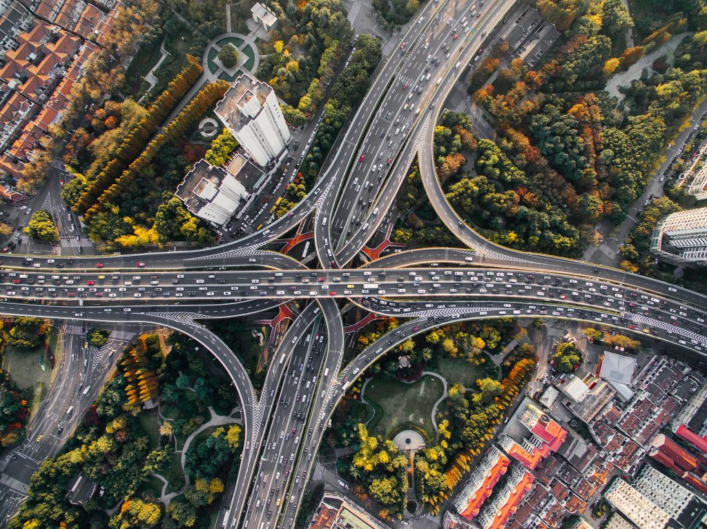 Photo of a an ariel view of a city with busy highways and green spaces teeming with biodiversity.