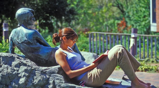 Summer school student sitting and ready outside on the Brandeis University campus