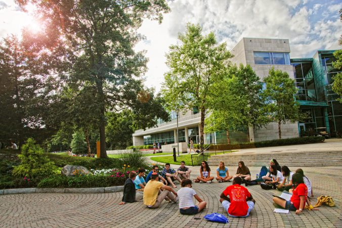 Students attending class outside on the Brandeis University campus.