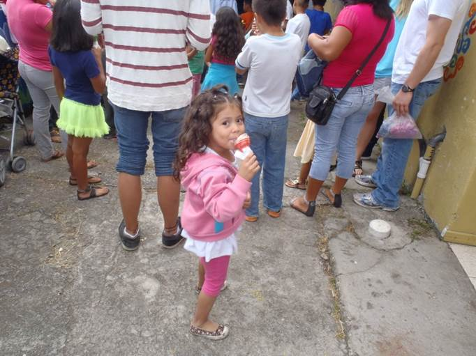 A child enjoying an ice cream cone outside of the FIMRC clinic in Alajuelita