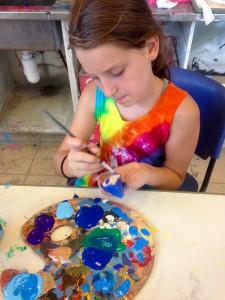 Ariel paints a rock from the garden at camp
