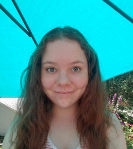 Caleigh standing under an umbrella on a sunny day.