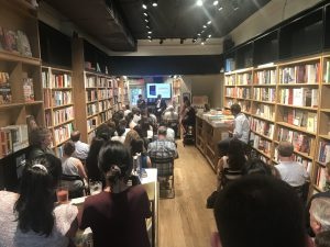 A room of people seated at a bookstore, with an interview happening at the front.
