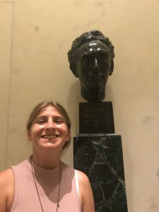 Renee posing with a bust of Louis D Brandeis