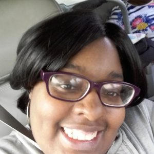 A close up shot of a woman smiling brightly at the camera. She has brown skin and short straight black hair. She is wearing silver hoops and burgundy glasses. She seems happy in the photo.