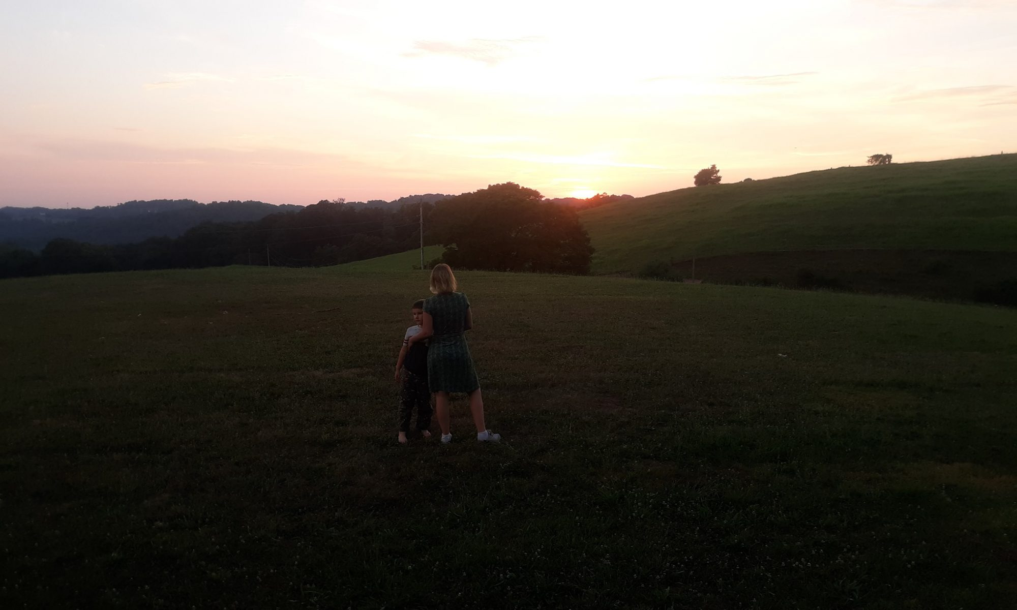 A photo of a blonde woman standing in a field with her son. The woman has her back to the camera and is wearing a green dress.